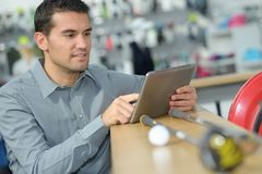 Man with digital tablet in hardware store. Man Royalty Free Stock Image