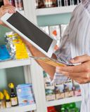 Man With Digital Tablet And Product In Supermarket Stock Photos