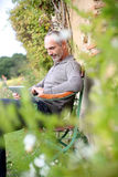 Man with digital tablet relaxing on bench Royalty Free Stock Images