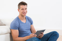 Man With Digital Tablet Sitting Near Sofa Royalty Free Stock Photos