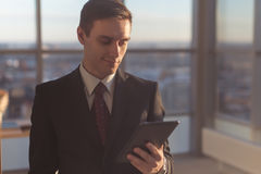 Man with digital tablet standing in modern office interior Royalty Free Stock Photography