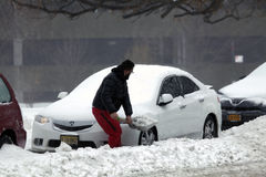 Man digs out car with shovel during snow storm Royalty Free Stock Image