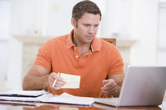 Man in dining room with laptop holding paperwork Royalty Free Stock Photo