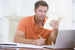 Man in dining room with laptop holding paperwork Royalty Free Stock Image