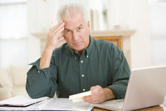 Man in dining room with laptop and paperwork Royalty Free Stock Images