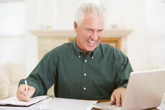 Man in dining room with laptop and paperwork Stock Image