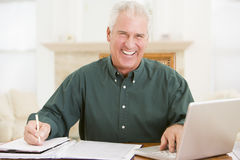 Man in dining room with laptop and paperwork Royalty Free Stock Image