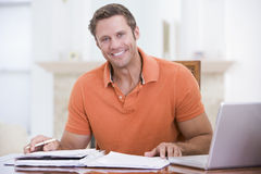 Man in dining room with laptop smiling Royalty Free Stock Images