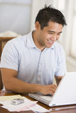 Man in dining room using laptop and smiling Stock Photography