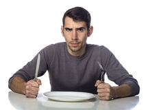 Man at dinner table with fork and knife raised. Royalty Free Stock Photo