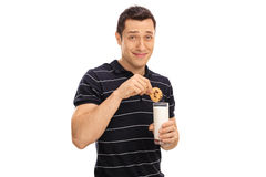 Man dipping a cookie in milk. Young man dipping a cookie in a glass of milk isolated on white background royalty free stock images