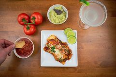 Enchiladas and margarita on wood table. Man dipping tortilla chip in salsa - mexican cuisine