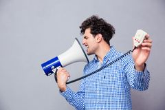 Man directing megaphone at herself Royalty Free Stock Images