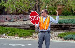 Man directs traffic at school crossing. September 2017 Denver CO USA; a man directs traffic outside a grade school to help keep kids safe while crossing the Stock Image