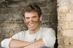 Man with dirty face doing DIY at home, sitting in brick fireplace, smiling, portrait Stock Photo