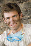 Man with dirty face doing DIY at home, wearing safety goggles, smiling, close-up, portrait Royalty Free Stock Photo