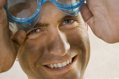 Man with dirty face wearing safety goggles, smiling, close-up, portrait Royalty Free Stock Photo