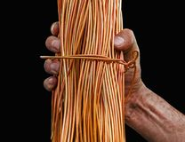 Man with dirty hands holding a roll of copper wire isolated on black. Background Stock Photos