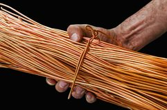 Man with dirty hands holding a roll of copper wire isolated on black. Background Stock Photo