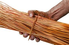 Man with dirty hands holding a roll of copper wire isolated on white. Background Royalty Free Stock Photography