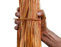 Man with dirty hands holding a roll of copper wire isolated on white. Background Stock Photography
