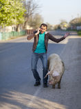 A man with a dirty pig Stock Image