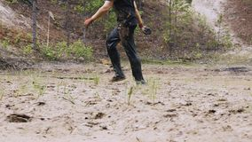 A man in a dirty race is walking in a muddy puddle.
