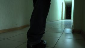 Shoes of a detective is walking on narrow corridor looking for necessary door