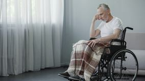 Man with disabilities sitting in wheelchair and thinking about illness, disease Royalty Free Stock Photos