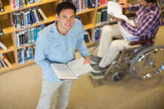 Man by disabled student in wheelchair in the library Stock Image