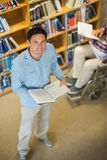 Man by disabled student in wheelchair in the library Stock Photo