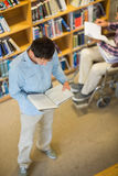 Man and disabled student in wheelchair reading books in library Stock Photography