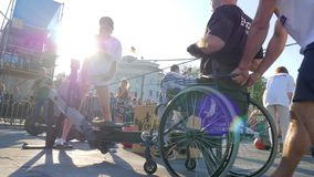 Man disabled on wheelchair pulls cable at training apparatus at sporting events in sunshine. Kherson, Ukraine 24 August 2017: man disabled on wheelchair pulls stock footage