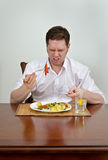 Man is disappointed with his dish Stock Image