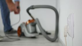 Man disconnecting vacuum cleaner from electrical socket stop cleaning the floor.  stock footage