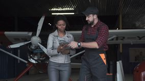 Man discussing in aircraft hangar with woman. Man discussing over digital tablet in aircraft hangar with woman stock video footage