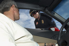 Man In Discussion With Police Officer. Man in car having discussion with police officer Royalty Free Stock Photos