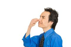 Man disgust on his face pinches his nose, something stinks bad smell stock photos