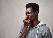 Man disgusted. Black man disgust face expressions portrait over gray background Royalty Free Stock Images