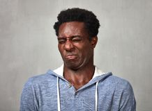 Man disgusted. Black man disgust face expressions portrait over gray background Stock Image