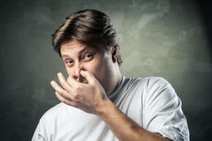 Man with disgusted expression closing his nostrils Royalty Free Stock Images