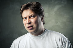 Man with disgusted expression over dark grey Stock Photography
