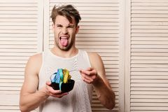 Man with disgusted face expression on background of beige jalousie. Guy in sleeveless shirt eating tape for measuring. Athlete with messy hair and unshaved stock images