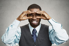 Man with disgusted face expression, looking through hand binoculars royalty free stock image