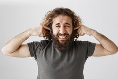 Man disgusted from loud neighbours. Sick and tired adult male with curly hair and beard shutting ears with index fingers. Grimacing from displeased emotions royalty free stock photography