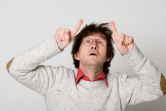 Man with disheveled hair pointing two fingers at something inter Royalty Free Stock Image