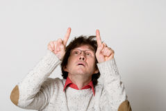 Man with disheveled hair pointing two fingers at something inter Royalty Free Stock Photography