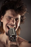 Man with disheveled hair singing into retro microphone Royalty Free Stock Images