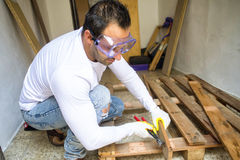 Man dismantled a pallet. With hammer and chisel Stock Images
