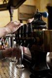 Man dispensing drought beer from generator Stock Images